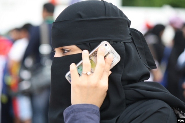 A woman uses a smartphone in Jeddah, Saudi Arabia, Jan. 28, 2016. Saudi Arabia and Iran accuse each other of human rights abuses against their own citizens. International rights groups say both countries have trampled on civil liberties, repressed women and committed other offenses. (H. Murdock/VOA)
