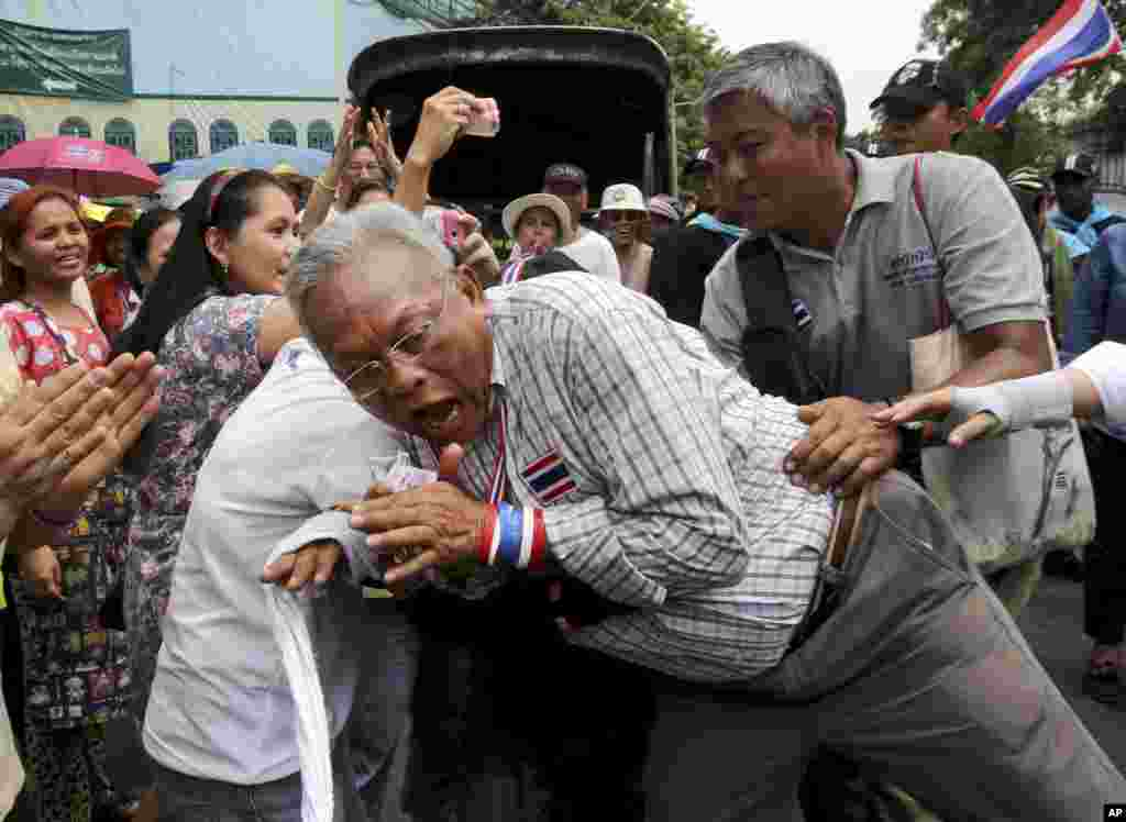 Leader of anti-government protesters Suthep Thaugsuban reacts as he is hugged by a supporter during a march in Bangkok, Thailand.