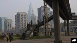 지난 4월 평양에서 주민들이 육교를 건너고 있다. 멀리 105층 피라미드 모양의 류경호텔이 보인다. 지난 1987년 착공했지만 아직도 건설 중이다.
