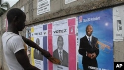 An unidentified man reacts to a campaign poster for incumbent President Laurent Gbagbo, as presidential campaigning kicked off 15 Oct 2010 in Abidjan
