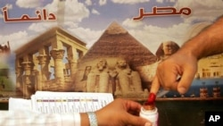 Once they cast their ballots, voters in Egypt dip their fingers in ink to indicate that they have voted (file photo)