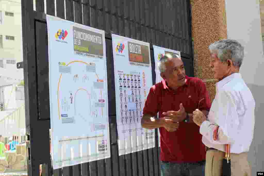 Una persona explica el proceso electoral a un elector en Venezuela en la mañana del domingo 7 de octubre. [Foto: Iscar Blanco, VOA]