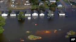 FILE - Floodwaters from Hurricane Florence surround homes in Dillon, S.C., Sept. 17, 2018. Scientists say climate change likely boosted rainfall totals for both Florence and 2017's Harvey.