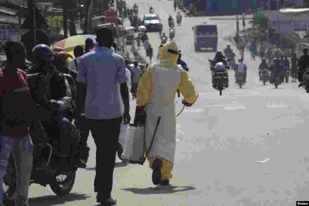 A health worker with disinfectant spray walks down a street outside the government hospital in Kenema, Sierra Leone, July 10, 2014.