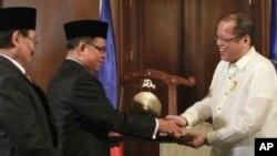 지난 15일 마닐라 대통령궁에서 열린 서명식에서 악수하는 베니그노 아키노 필리핀 대통령(오른쪽)과 무라드 에브라힘 모로이슬람해방전선 지도자.
