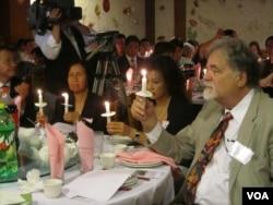国际特赦组织中国专员齐摩门( 右一 )点起蜡烛纪念六四(美国之音容易拍摄)