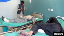 Afghan men receive treatment at a hospital after a suicide car bomber and gunmen attacked a provincial Afghan police headquarters in Gardez, the capital of Paktia province, Afghanistan, Oct. 17, 2017.