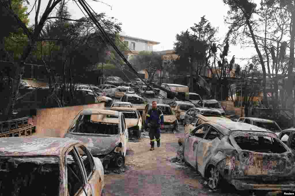 대형 산불이 발생한 그리스 아테네 인근 '마티'의 해변 마을에서 소방대원이 불에 탄 차들 사이로 걷고 있다.