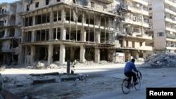 19일 시리아 반군이 점령한 알레포 알수카리 지구에서, 자전거에 탄 주민이 부서진 건물 사이를 지나고 있다.