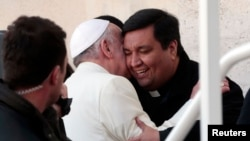 Fabian Baez, a priest from a church in downtown Buenos Aires, is greeted by Pope Francis at the end of the Wednesday general audience in Saint Peter's square at the Vatican, Jan. 8, 2014.
