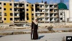 4일 알레포 동부 하나노 지역에서 한 여성이 목발을 집고 불에 탄 집으로 돌아오고 있다.