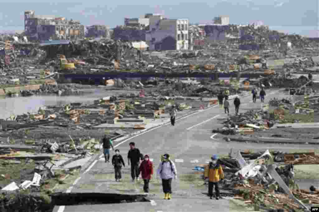 People walk a road between the rubble of destroyed buildings in Minamisanriku town, Miyagi Prefecture, northern Japan, Monday, March 14, 2011, three days after a powerful earthquake-triggered tsunami hit the country's east coast. (AP Photo/The Yomiuri Shi