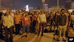 Erdem Gunduz, left, and dozens of people stand silently on Taksim Square in Istanbul early Tuesday, June 18, 2013.