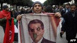 Một người cầm bức hình bị đốt của cựu Tổng thống Ben Ali, trong cuộc biểu tình đòi loại bỏ giới chức chế độ cũ ra khỏi chính phủ