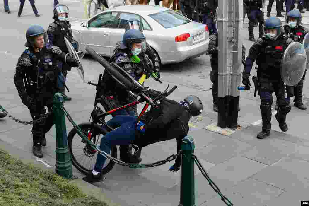 A demonstrator is handled as police officers disperse a protest against Covid-19 regulations in Melbourne, Australia.