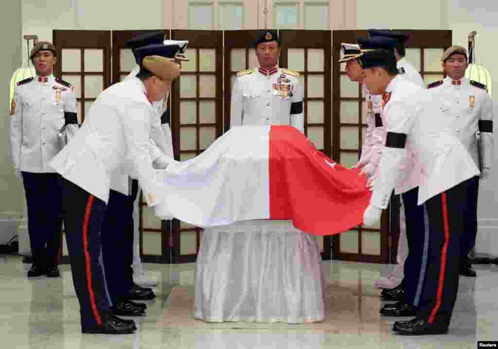 The Guard of honor drapes the Singapore's national flag over the coffin of the late first Prime Minister Lee Kuan Yew in the Istana before he is conveyed to the Parliament House where he will lie in state until March 28.