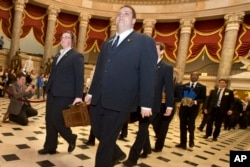 Pages lead a Senate procession carrying two boxes holding Electoral College votes through Statuary Hall to the House Chamber on Capitol Hill on Capitol Hill in Washington, Friday, Jan. 4, 2013, for the counting of the votes