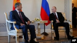 Russian President Vladimir Putin (R) and Kyrgyz President Almazbek Atambayev speak during their meeting in the Konstantin Palace outside St. Petersburg, Russia, March 16, 2015.