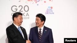 日本首相安倍晋三与中国国家主席习近平在日本大阪出席G20峰会时握手。(2019年6月28日)