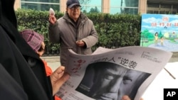 "FILE - A Chinese man holds up a Chinese newspaper with the front-page photo of Donald Trump and the headline ""Outsider counter attack"" at a newsstand in Beijing, China, Nov. 10, 2016. China has pledged to ""firmly defend its legitimate rights and interests"" regarding U.S. tariffs on steel and aluminum."