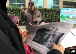 "FILE - A man holds a Chinese newspaper with a front page photo of U.S. President Donald Trump at a newsstand in Beijing, China, Nov. 10, 2016. China has pledged to ""firmly defend its legitimate rights and interests"" in response to metal tariffs intruduced by the Trump administration."