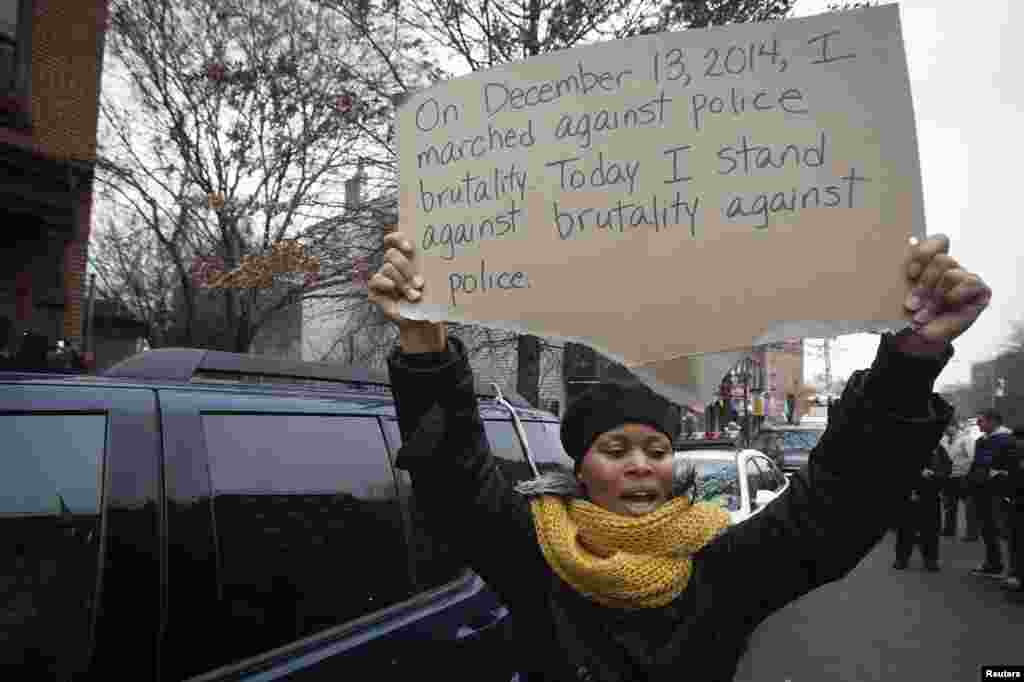 A woman holds up a sign at a makeshift memorial at the site where two police officers were shot in the head in the Brooklyn borough of New York, Dec. 22, 2014.