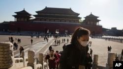 18일 중국 베이징의 관광명소 자금성을 방문한 여성이 마스크를 쓰고 있다.