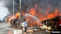 12일 잠보앙가시에서 시민이 공격으로 불이난 집에 물을 뿌리고 있다.