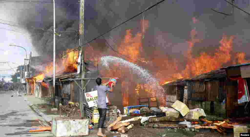A man throws water into a burning house in Zamboanga, Philippines, Sept. 12, 2013.