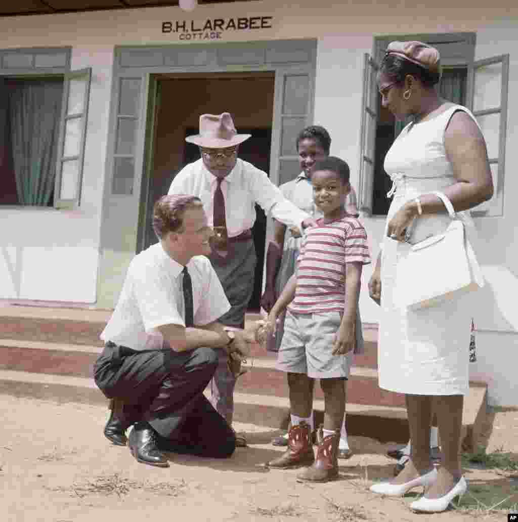 Billy Graham, évangéliste américain, parle avec des enfants du village de Virginia, à 30 kilomètres de Monrovia en 1960.
