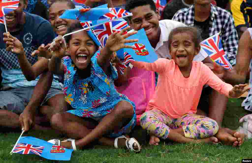 Children wave flags as Britain's Prince Harry and Meghan, Duchess of Sussex, arrive in Suva, Fiji.