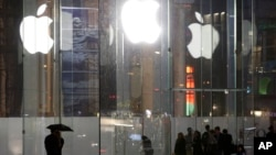 FILE - Pedestrians pass the Apple store location on Fifth Avenue in New York, June 6, 2013.