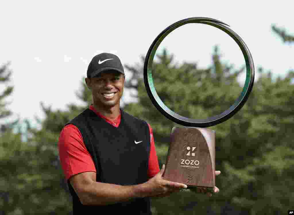 តារាវាយកូនហ្គោលលោក Tiger Woods ឈរថតជាមួយនឹងពានរង្វាន់បន្ទាប់ពីឈ្នះការប្រកួតវាយកូនហ្គោល Zozo Championship PGA Tour នៅក្រុង Inzai ប្រទេសជប៉ុន។