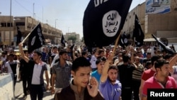 File - Demonstrators chant pro-Islamic State group slogans as they wave the group's flags in front of the provincial government headquarters in Mosul, Iraq, June 2014.