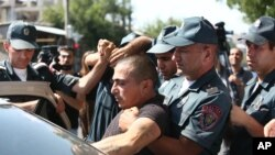 Armenian police detain an unidentified man in Yerevan, Armenia, June 17, 2016. Armed supporters of a jailed opposition leader attacked a police station in Armenia's capital on Sunday.