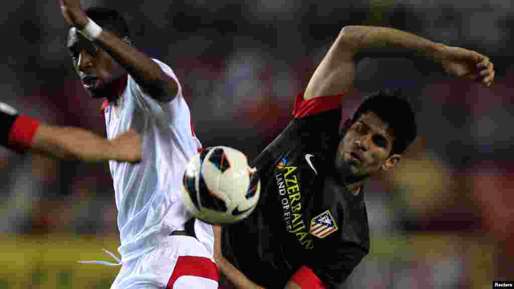 Sevilla's Geoffrey Kondogbia (L) and Atleatico Madrid's Diego Costa battle for the ball during their Spanish First Division soccer match at Ramon Sanchez Pizjuan stadium in Seville April 21, 2013.
