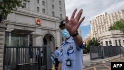 當押送任志強的警車抵達北京第二中級人民法院時一名警察在向記者做手式。 (2020年9月11日)
