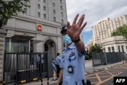 当押送任志强的警车抵达北京第二中级人民法院时一名警察在向记者做手式。(2020年9月11日)