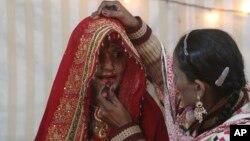 Seorang perempuan memberi hiasan wajah kepada calon pengantin Hindu sebelum pernikahannya di Karachi, Pakistan (foto: ilustrasi). Pakistan meloloskan UU baru untuk melindungi hak perkawinan masyarakat minoritas Hindu.