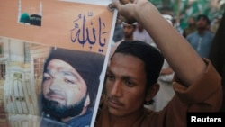 FILE - A supporter of a religious political party holds a banner of convicted killer Mumtaz Qadri during a demonstration against Qadri's sentence, in Karachi, March 9, 2015.