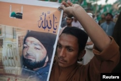 FILE - A supporter of a religious political party holds a banner of convicted killer Mumtaz Qadri during a demonstration against Qadri's sentence, in Karachi, Pakistan, March 9, 2015.