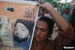 ຜູ້ສະໜັບສະໜູນ ພັກການເມືອງສາສະໜາ ຄົນໜຶ່ງ ຖືປ້າຍ ຮູບພາບ ຂອງທ້າວ Mumtaz Qadri ຜູ້ຖືກຕັດສິນວ່າຜິດ ໃນຂໍຫາຂ້າຄົນ ໃນລະຫວ່າງ ການເດີນຂະບວນປະທ້ວງ ຕໍ່ຕ້ານຄຳຕັດສິນ ຂອງທ້າວ Qadri ຢູ່ໃນນະຄອນ Karachi ປະເທດປາກິສຖານ, ວັນທີ 9 ມີນາ 2015.