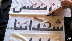 In this picture sent secretly to a VOA e-mail account, Libyan anti-government activists sew the flag of the revolution. The banner reads, 'We will never forget our martyrs'