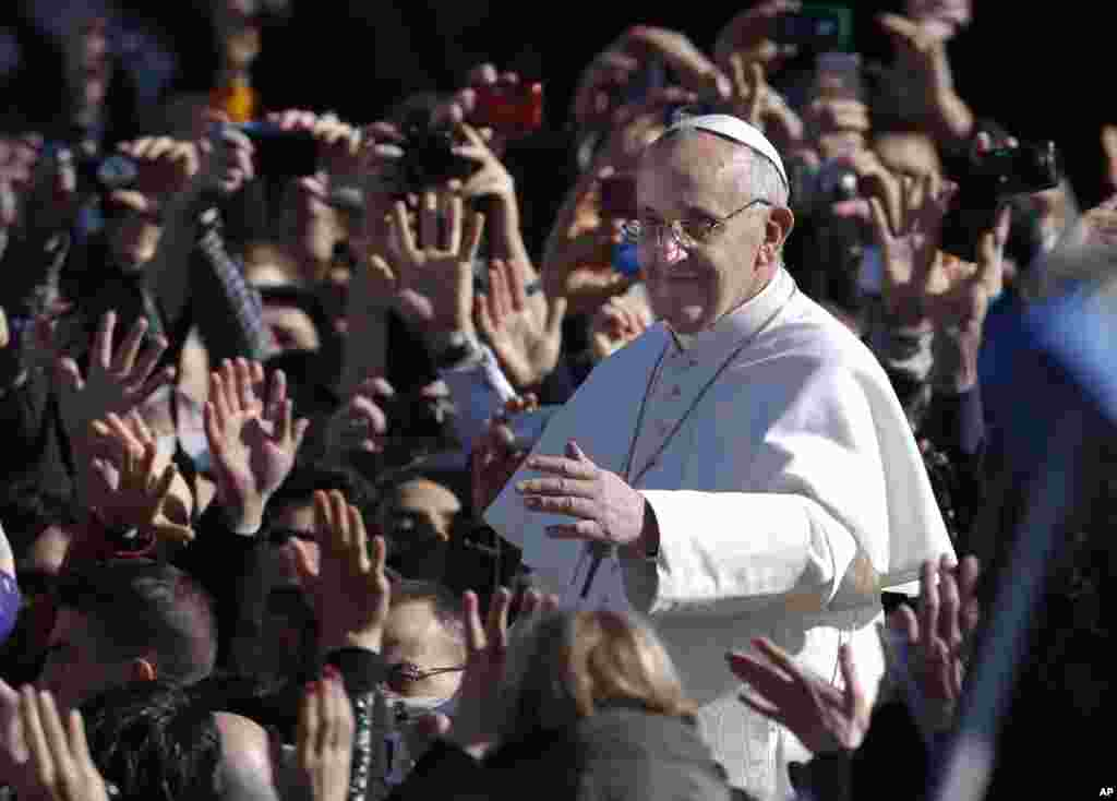 Pope Francis waves as he arrives in Saint Peter's Square for his inaugural mass at the Vatican, March 19, 2013.