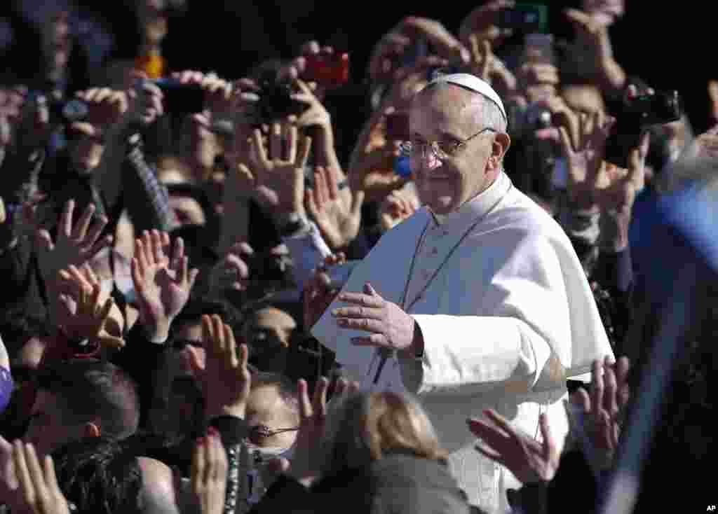 Papa Francis akiwapungia mkono waumini alipokuwa anawasili kwenye uwanja wa Saint Peter huko Vatican kwa ajili ya sherehe za kuapishwa kwake, March 19, 2013.