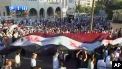 "Image from amateur video made available by Shamsnn on August 30, 2011 shows protesters carrying a large Syrian flag with the words ""Freedom, Syria"" written on it in Arabic in Idlib. (The contents of this image cannot be independently verified.)"