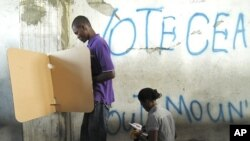 People mark their ballots during presidential elections in Port-au-Prince, March 21, 2011