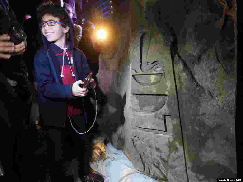 An Egyptian child takes an image of the carving found on the back of the statue that was discovered recently in Matarya that almost certainly depicts Psamtik I, March 16, 2017. (H. Elrasam/VOA)