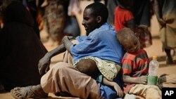 បុរសជាតិសូម៉ាលីម្នាក់ភៀសខ្លួនពីការរាំងស្ងួតនៅក្នុងប្រទេសជាមួយគ្រួសារ អង្គុយផ្ទាល់ដីនៅខាងក្រៅកន្លែងចែកអាហារក្នុងជំរំជនភៀសខ្លួន Dadaab ក្នុងតំបន់ឦសាននៃប្រទេសកេនយ៉ា នៅថ្ងៃទី៥ខែកក្កដាឆ្នាំ២០១១។