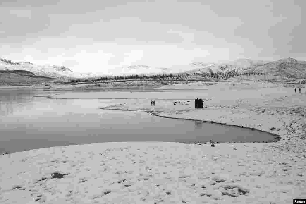 Warga Pakistan mengunjungi danau Hanna saat salju turun di kota Quetta.